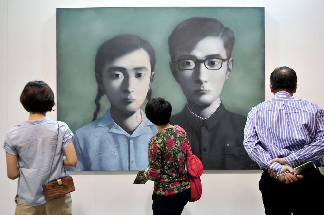 "TO GO WITH: Culture-HongKong-art-business by Stephen Coates Visitors look at a painting by Chinese artist Zhang Xiaogang titled ""Brother and Sister"" during the soft opening of the Hong Kong International Art Fair in Hong Kong on May 16, 2012. The event known as Art HK opened to the public on May 17, featuring works by top international artists from Picasso to Chinese dissident Ai Weiwei and cementing the city's status as a global art hub. AFP PHOTO / Philippe Lopez (Photo credit should read PHILIPPE LOPEZ/AFP/GettyImages)"